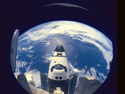 The Space Shuttle Atlantis is back-dropped against Earth.